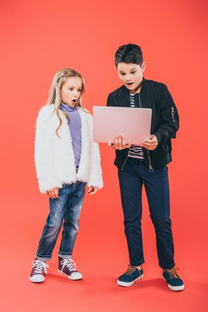 full length view of two shocked kids using laptop on red Stock Photo