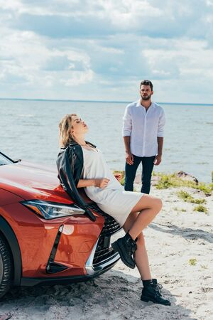 attractive woman in dress with closed eyes lying on car and man look at her