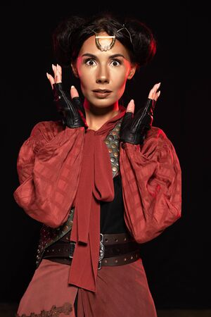front view of attractive surprised steampunk woman in leather gloves isolated on black