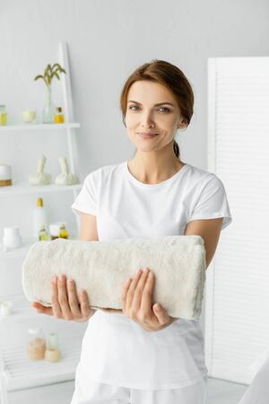 attractive masseur holding white towel and looking at camera