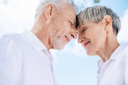 smiling senior couple touching foreheads with closed eyes under blue sky