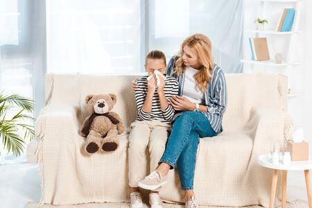 mother sitting with sick daughter sneezing in tissue