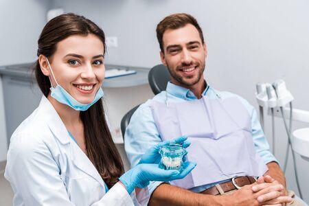 El enfoque selectivo del dentista atractivo en guantes de látex sosteniendo el modelo de dientes cerca del paciente con las manos apretadas Foto de archivo