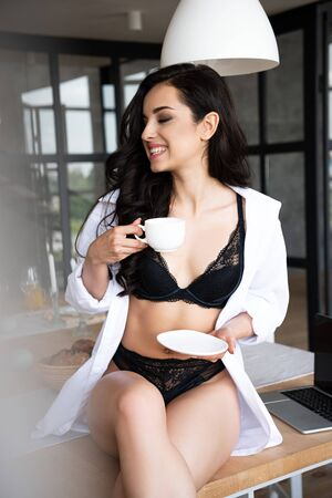 sexy girl in black underwear and white shirt drinking coffee with closed eyes while sitting on table in kitchen