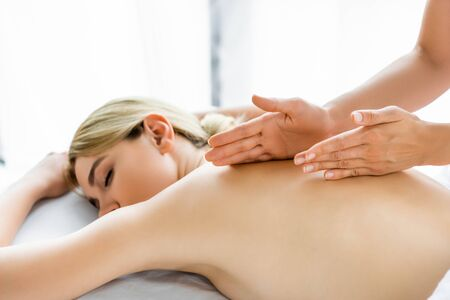 cropped view of masseur doing back massage to attractive woman in spa