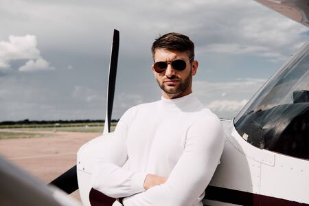 man in sunglasses standing with crossed arms near plane in sunny day
