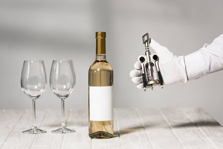 cropped view of waiter in white glove holding corkscrew near table with bottle of wine and wine glasses