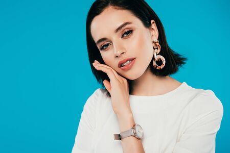 woman in dress in earring and wristwatch with hand near face isolated on blue Stock Photo