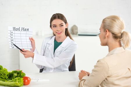 smiling dietitian in white coat holding meal plan and patient at table