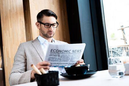 Empresario centrado en gafas leyendo el periódico en el café