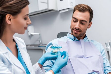 selective focus of man looking at teeth model in hands of attractive dentist