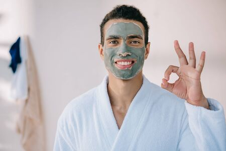 handsome man with face mask and in bathrobe showing okay sign and looking at camera