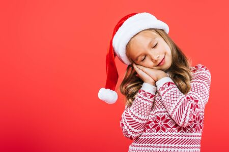 kid in sweater and santa hat sleeping isolated on red