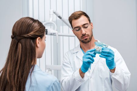 selective focus of bearded dentist in glasses holding tooth model near patient 写真素材