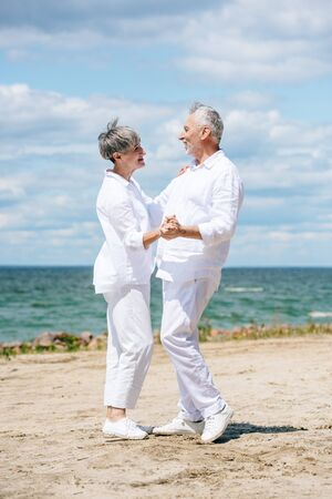 full length view of happy senior couple looking at each other while dancing at beach Standard-Bild