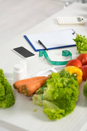 clipboard with pen, measure tape, smartphone with blank screen, calculator, medicine and fresh vegetables on table