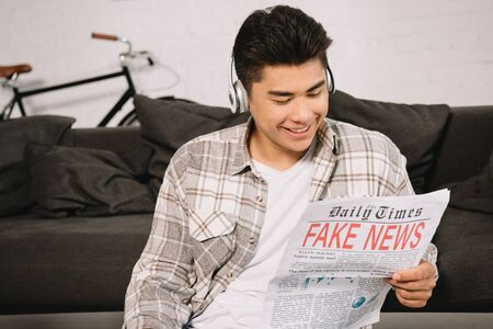young asian man in headphones smiling while reading fake news newspaper 스톡 콘텐츠