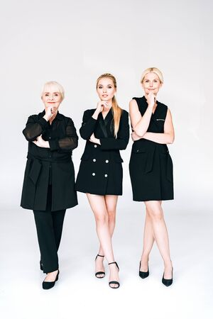 full length view of fashionable three-generation blonde women in total black outfits posing isolated on grey