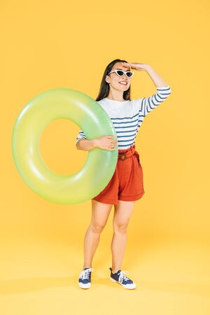 pretty asain woman in sunglasses holding swim ring and looking away on yellow background