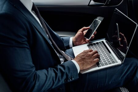 cropped view of african american businessman using laptop and smartphone in car