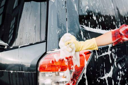 cropped view of girl in latex glove near wet car in foam