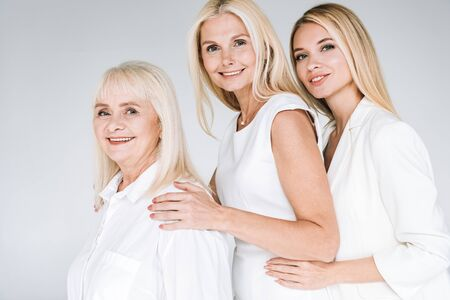 side view of three generation blonde women isolated on grey
