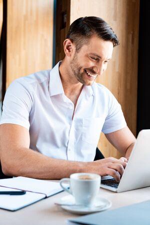 smiling freelancer typing on laptop keyboard in cafe