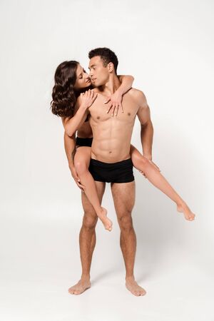 handsome muscular man piggybacking attractive sexy woman on white