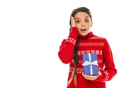 surprised kid in sweater holding present and touching head isolated on white
