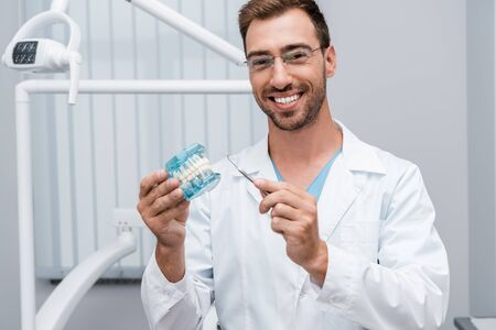 cheerful dentist in glasses holding dental instrument and tooth model in hands 写真素材