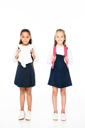 full length view of two adorable multicultural schoolgirls smiling at camera on white background