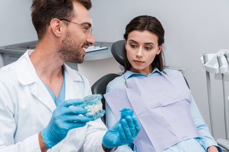 selective focus of handsome bearded man holding retainer and tooth model near attractive patient 写真素材