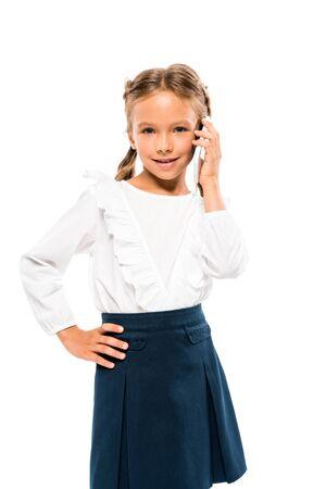 Lindo niño de pie con la mano en la cadera y hablando por teléfono inteligente aislado en blanco