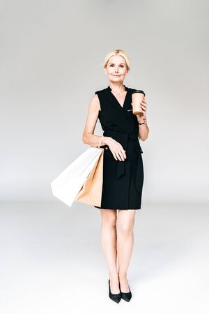 full length view of elegant blonde woman in black outfit with shopping bags and coffee to go isolated on grey