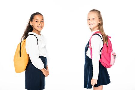 two cheerful multicultural schoolgirls with backpacks looking at camera isolated on white
