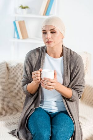 sick woman with head scarf holding cup with tea
