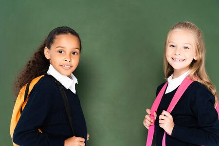 two smiling miltucultural schoolgirls smiling at camera while standing near green chalkboard