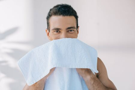muscular young man wiping face with blue towel and looking at camera