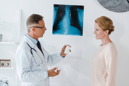 handsome doctor in glasses standing near x-ray and holding bottle near cheerful woman