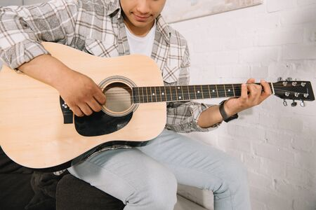 cropped view of young man playing acoustic guitar at home