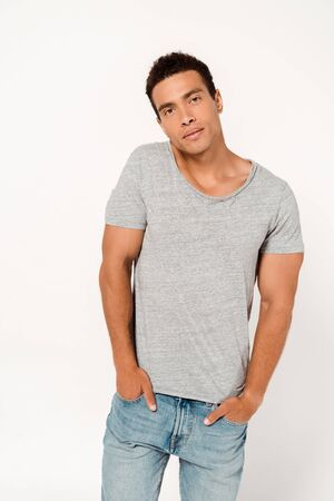 handsome mixed race man standing with hands in pockets and looking at camera on white