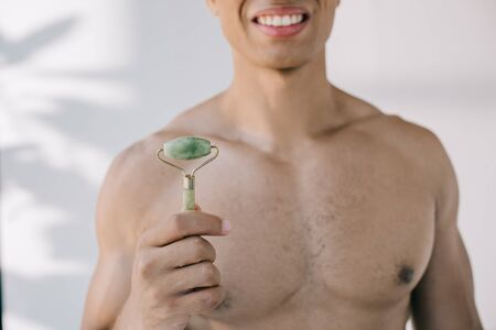 cropped view of mixed race man presenting stone jade roller and smiling while looking at camera