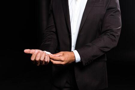 vista ritagliata dell'uomo di razza mista che tocca la camicia bianca isolata sul nero