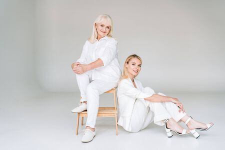 full length view of smiling blonde grandmother sitting on chair near granddaughter in total white clothes