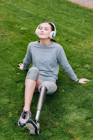 disabled sportswoman sitting on grass and listening music in headphones