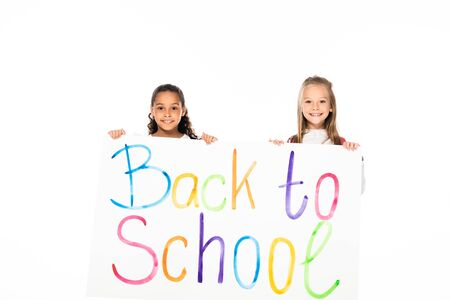 two adorable multicultural schoolgirls holding placard with back to school inscription isolated on white 写真素材