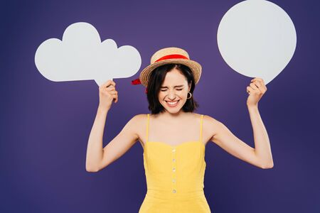 happy girl in straw hat holding empty white thought and speech bubbles isolated on purple
