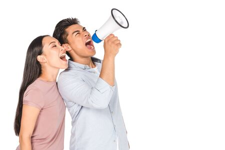 young asian couple screaming into megaphone together isolated on white Imagens