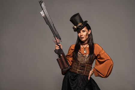 attractive steampunk woman in top hat holding gun and standing with hand on hip isolated on grey