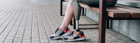 panoramic shot of disabled sportswoman with prosthetic leg on street